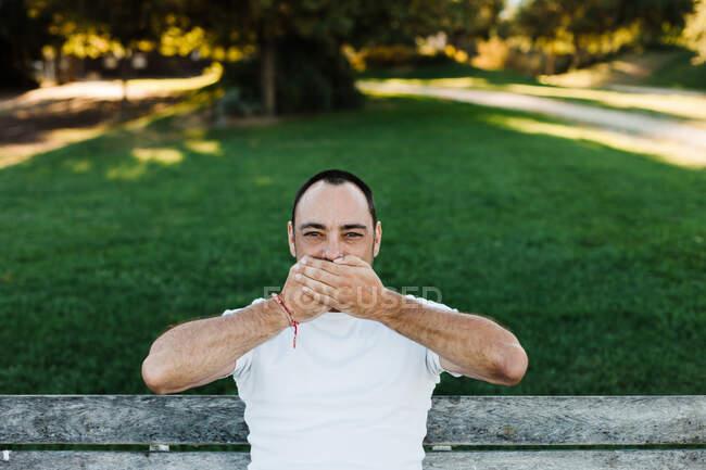 Atractivo macho adulto cubriendo la boca mientras está sentado en el banco en el parque en el día soleado - foto de stock