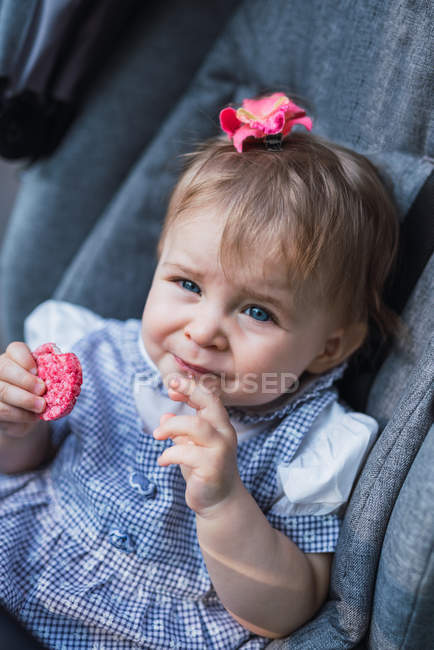 Lovely baby girl looking at camera and eating sweet cookie while sitting in comfortable carriage — Stock Photo