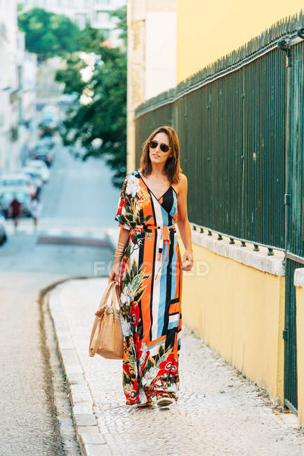 Elegant woman in long dress carrying handbag and walking on street in sunlight — Stock Photo