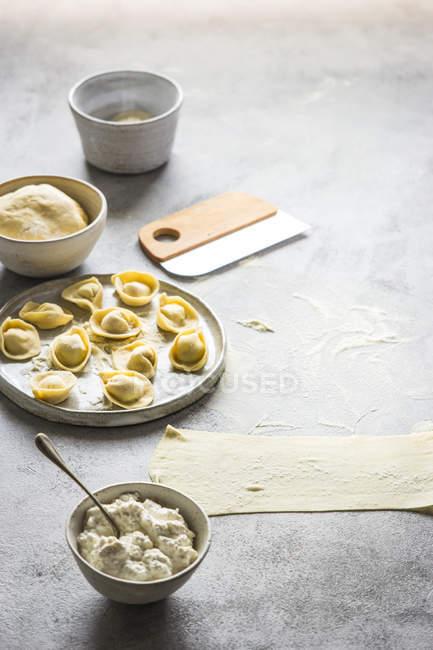 Тесто и миску творог при подготовке тортеллини на серый настольные — стоковое фото