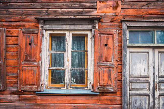 Small window with shutters and shabby door of old lumber house — Stock Photo