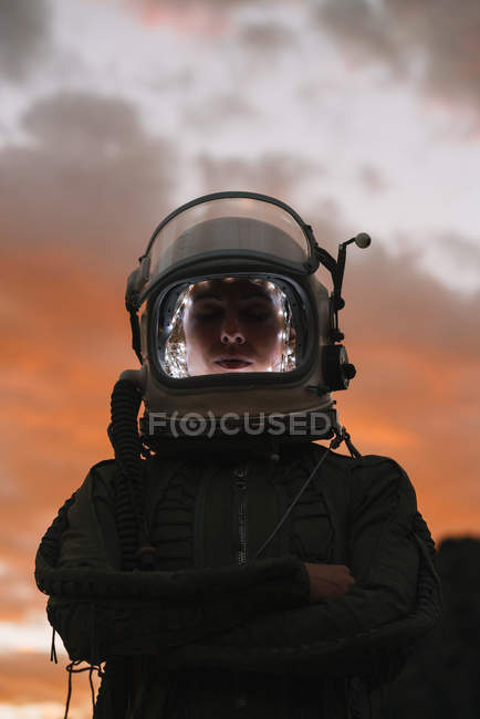 Girl wearing old space helmet and spacesuit against dramatic sky at sunset — Stock Photo