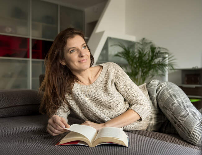 Lovely adult lady in elegant outfit smiling and looking away while lying on comfortable sofa with interesting book — Stock Photo
