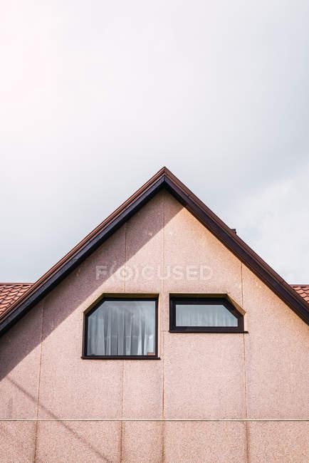 Due finestre sagomate insolite su parete sotto tetto di casa di campagna contro cielo nuvoloso — Foto stock