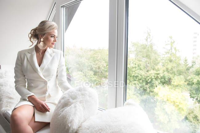Mulher bonita nova na jaqueta branca com penteado clássico sentado na soleira da janela com travesseiros macios e olhando através da janela — Fotografia de Stock