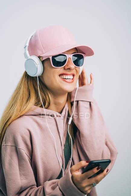 Mulher elegante com capuz rosa e boné ouvindo música com fones de ouvido — Fotografia de Stock