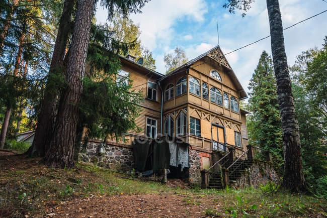Grande casa in legno situata sulla collina nella foresta — Foto stock