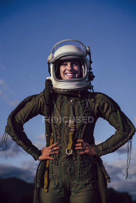 Confident smiling female astronaut standing in nature in evening — Stock Photo