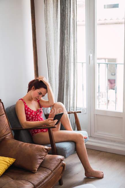 Молодая женщина в Красный купальник, сидя в кресле в зале и с помощью смартфона — стоковое фото