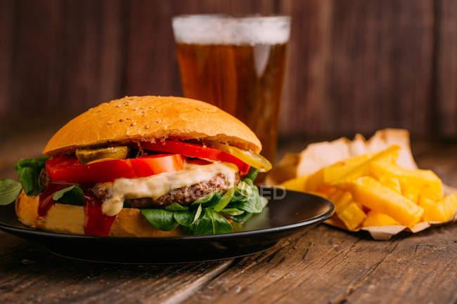 Смачні гурманів бургер на тарілку, на темному тлі дерев'яні з пивом і Фрис — стокове фото