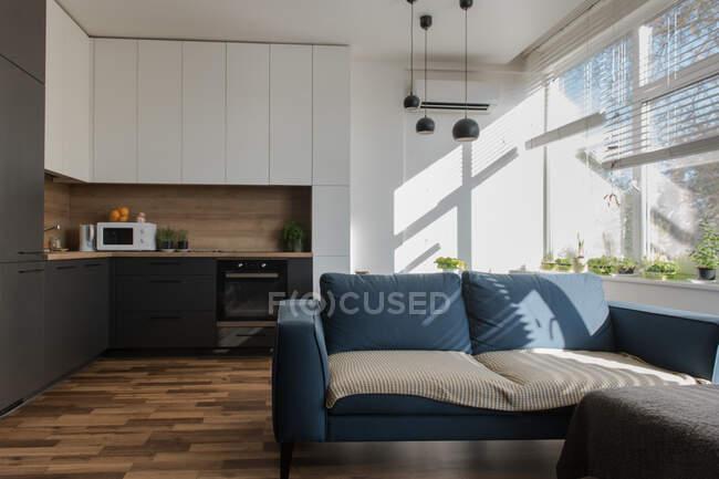 Удобный диван, стоящий рядом с кухонной мебелью в стильной комнате современной квартиры в солнечный день — стоковое фото