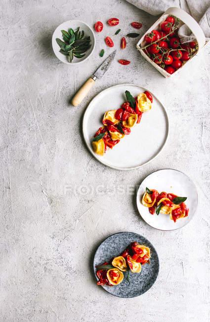 Teller mit servierten Tortellini mit Tomaten auf grauer Tischplatte — Stockfoto