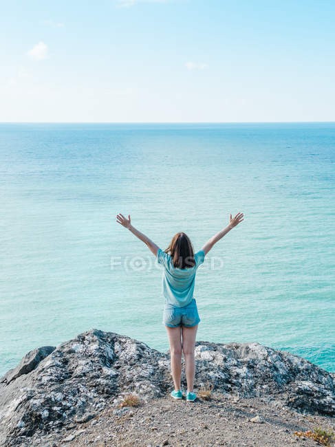 Woman in shorts standing on edge of cliff above endless blue sea water — Stock Photo