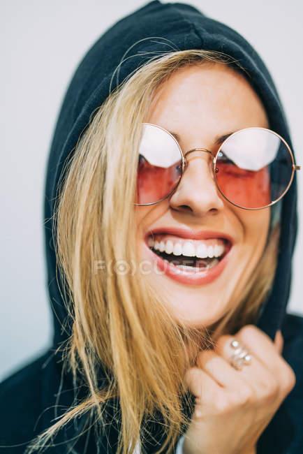 Jovem loira de óculos de sol e capuz rindo no fundo branco — Fotografia de Stock