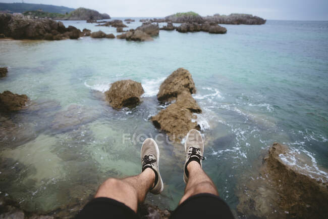 From above shot of legs of anonymous man hanging over beautiful sea water on beach in Cantabria, Spain — Stock Photo