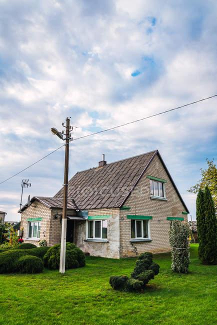 Электрические столбы и провода возле старой кирпичной хижины в сельской местности — стоковое фото