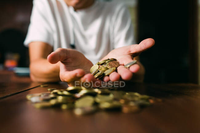 Unrecognizable guy in white T-shirt holding handful of coins over timber tabletop — Stock Photo