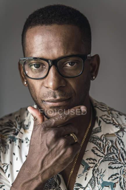 Portrait de grave afro-américain dans accessoires dorés et verres à toucher le menton — Photo de stock