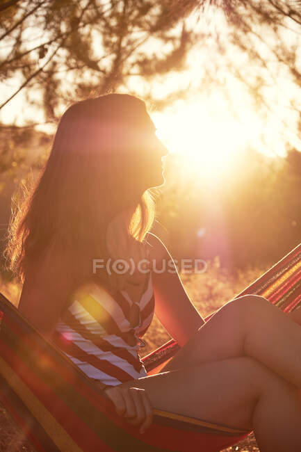 Tanned female on hammock at sunny glade — Stock Photo