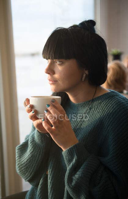 Woman looking out through the window — Stock Photo
