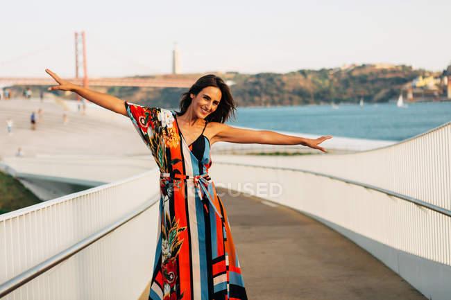 Элегантная женщина в платье стоя на мосту с оружием протянутой в солнечном свете — стоковое фото