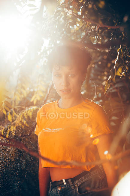 Portrait of sensual brunette woman with short hair standing in green vegetation with sunlight — Stock Photo