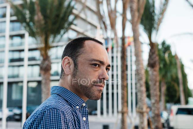 Vue latérale d'attrayant homme adulte en chemise à carreaux regardant loin tout en se tenant sur fond flou de la rue de la ville moderne — Photo de stock