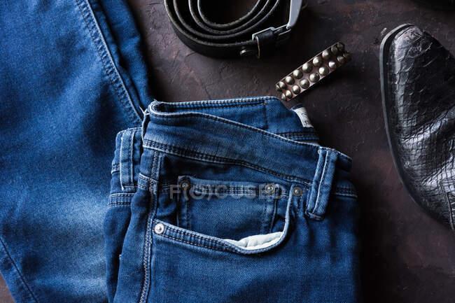 Вид с воздуха мужской джинсовой одежды с кошельком, браслетом, смартфоном. и черная кожаная обувь — стоковое фото