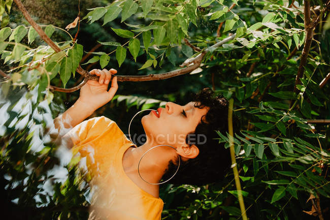 Thoughtful sensual brunette with short hair standing in green vegetation with sunlight — Stock Photo