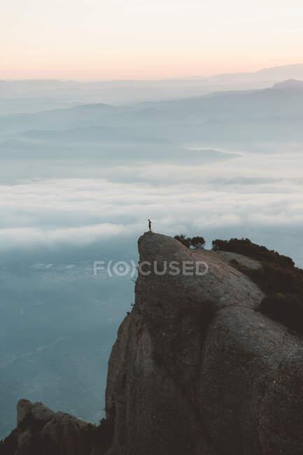 Силует невпізнаної людини, що стоїть на скелі під час величного сходу сонця в хмарному ранку в Барселоні (Іспанія). — стокове фото