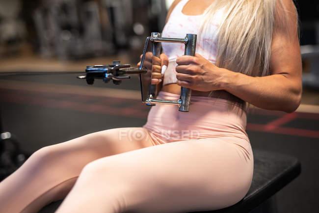 Femme blonde athlétique, faire des exercices sur appareils d'entraînement — Photo de stock