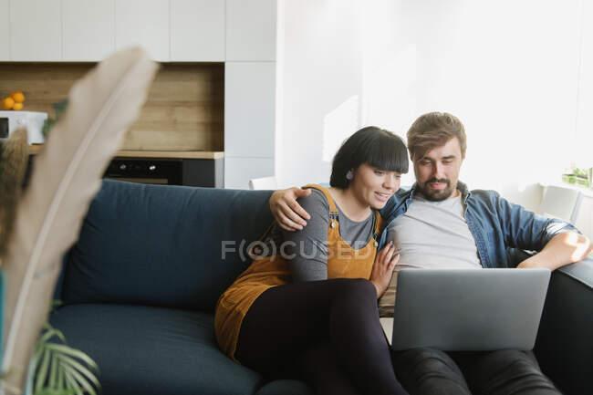 Молодий чоловік і жінка обіймаються і насолоджуються хорошою плівкою на ноутбуці, сидячи на зручному дивані в затишній вітальні. — стокове фото