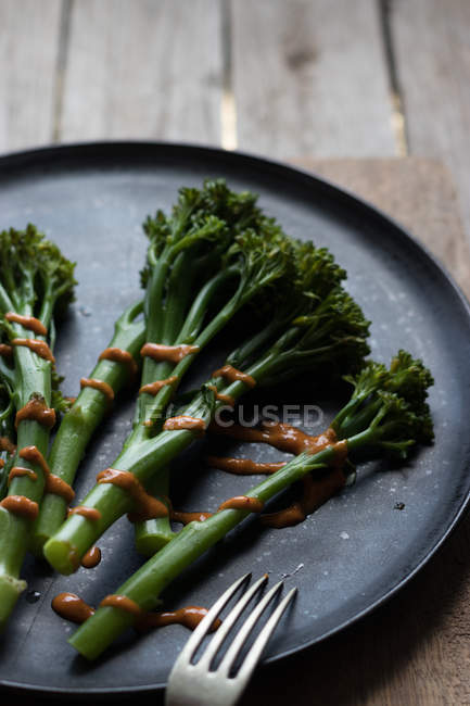 Close-up of steamed broccoli with romesco sauce on black plate on wooden table — Stock Photo