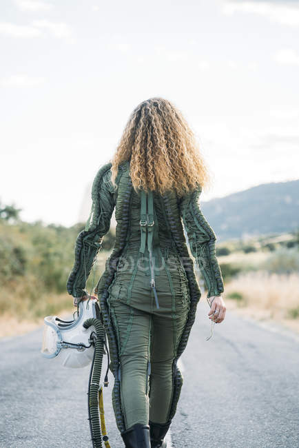 Back view of woman wearing astronaut costume walking along countryside road — Stock Photo