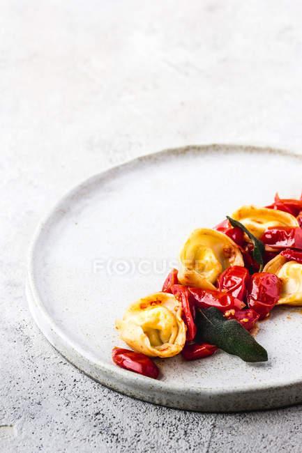 Délicieux plat de tortellini aux tomates servi sur plaque sur le dessus de table gris — Photo de stock