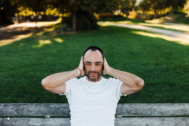 Attractive adult male covering ears while sitting on bench in park on sunny day — Stock Photo