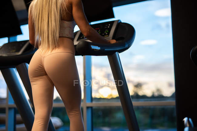 Fit sportswoman in sportswear doing exercise on treadmill in gym in front of window — Stock Photo