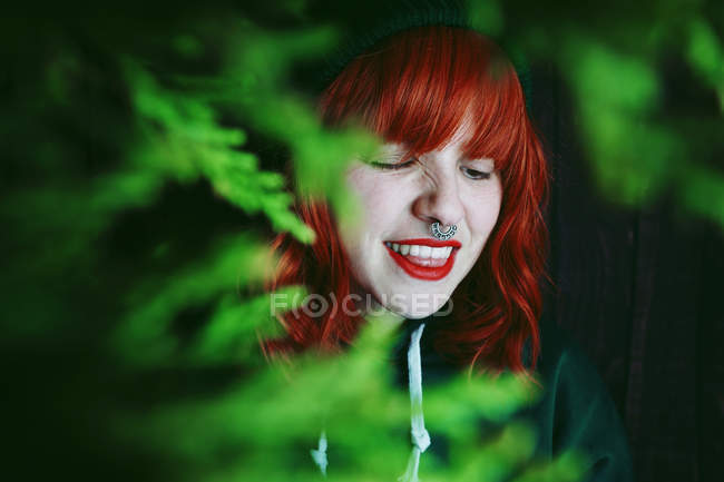 Crinkling young red haired woman between fir twigs on black background — Stock Photo