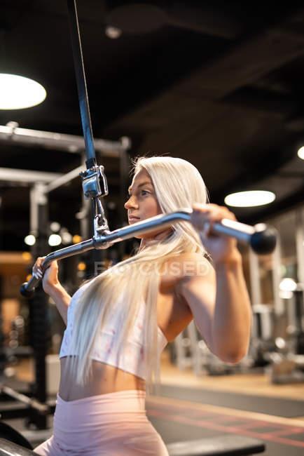 Donna bionda atletica facendo esercizio in palestra — Foto stock