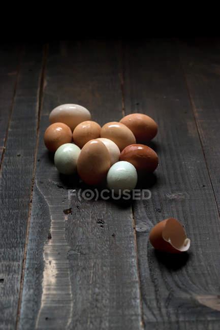 Haufen weißer und brauner Eier mit feuchter Schale auf dunklem Holztisch — Stockfoto