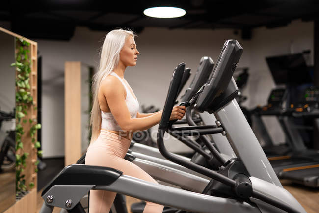 Blond young woman in sportswear doing exercise on stepper in gym — Stock Photo