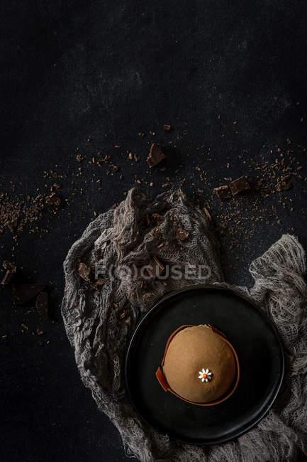 Schokoladenkuchen, garniert mit Daisy Blumen auf dunklem Hintergrund — Stockfoto