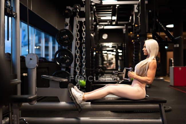 Athlétique jeune femme blonde, faire des exercices sur appareils d'entraînement — Photo de stock