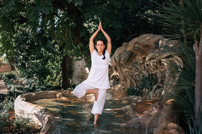 Женщина, стоящая в фонтанной воде в дереве, позирует во время занятий йогой в парке — стоковое фото