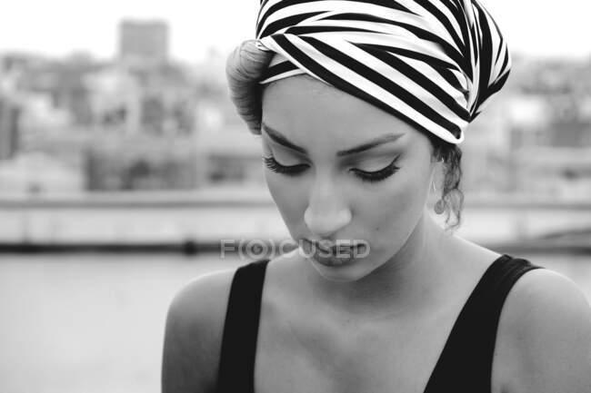 Молодая привлекательная женщина с полосатым платком на голове, стоящая на крыше и смотрящая сверху на размытый фон города — стоковое фото