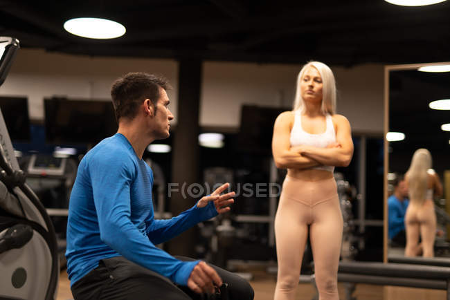 Young man in blue pullover and woman with blond hair in sportswear talking in gym near equipment and mirror — Stock Photo
