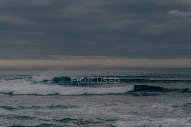 Mare blu grezzo con onde alte su sfondo di cielo nuvoloso cupo — Foto stock