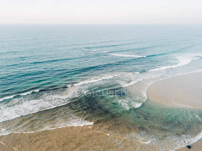 Sandy beach washed by sea water — Stock Photo