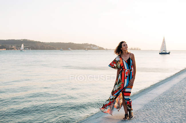 Content woman in long colorful dress walking on cobblestone promenade at sunset against seascape — Stock Photo