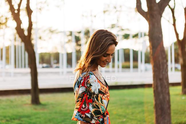 Elegante lächelnde brünette Frau in buntem Kleid steht im Stadtpark und schaut nach unten — Stockfoto